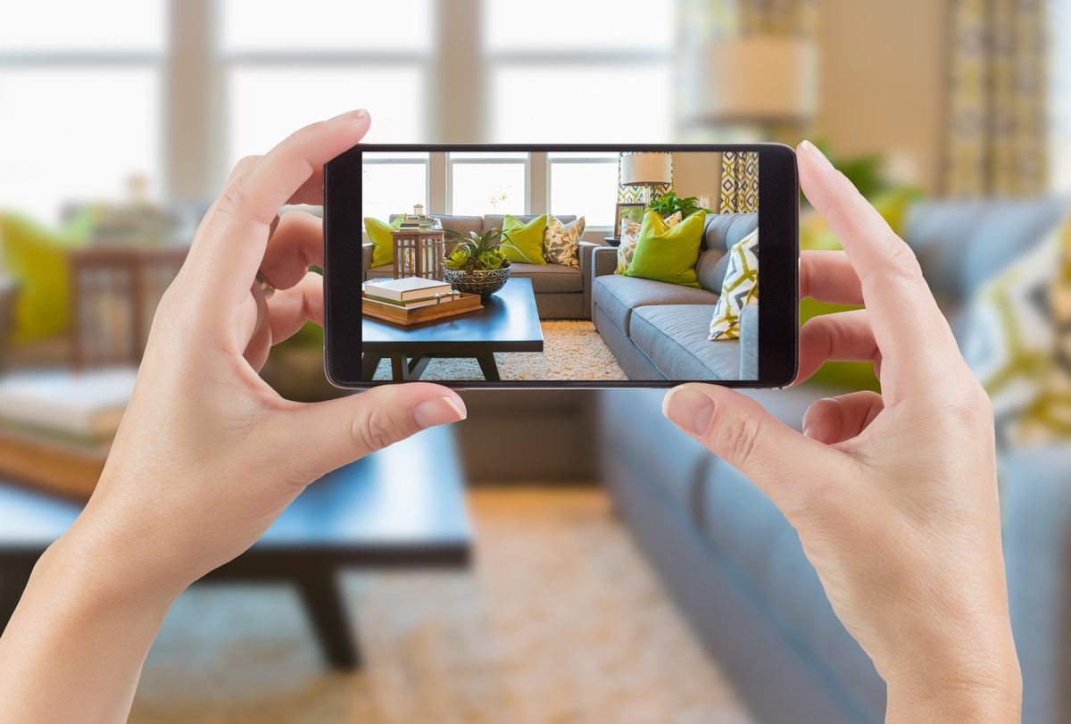 FemSmart Phone Displaying Photo of House Interior Living Room Behind.